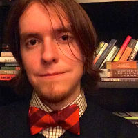 A headshot of Andrew Kulak earing an orange and maroon Virginia Tech bowtie in front of a bookshelf.